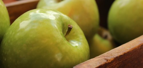 green apples piled into a box