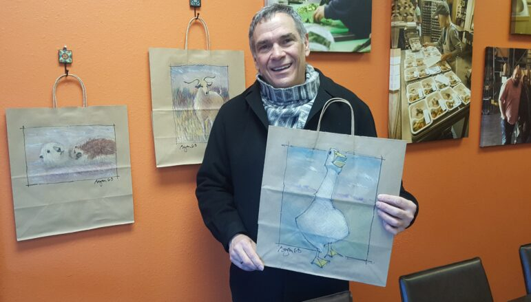 Bryan Aumiller poses with his decorated meal bags, which feature sketches of an otter, sheep, and goose