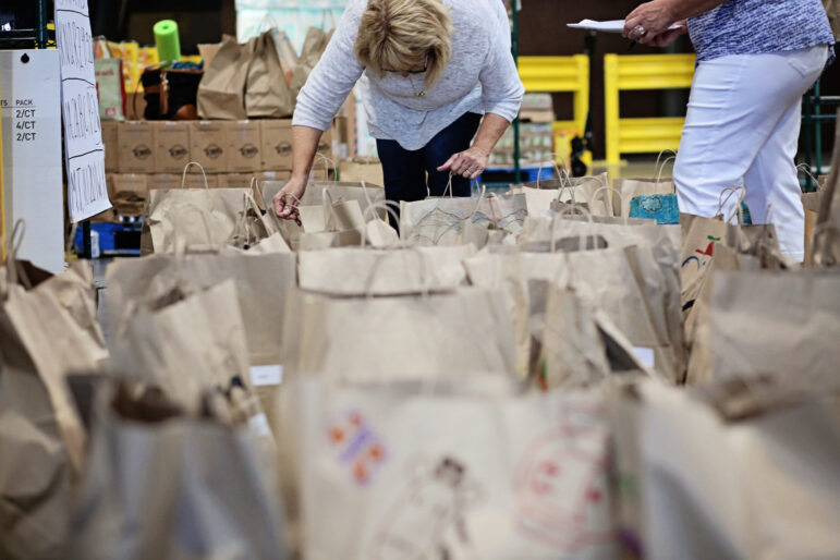 A volunteer looks into meal bags spread out on the floor of a warehouse