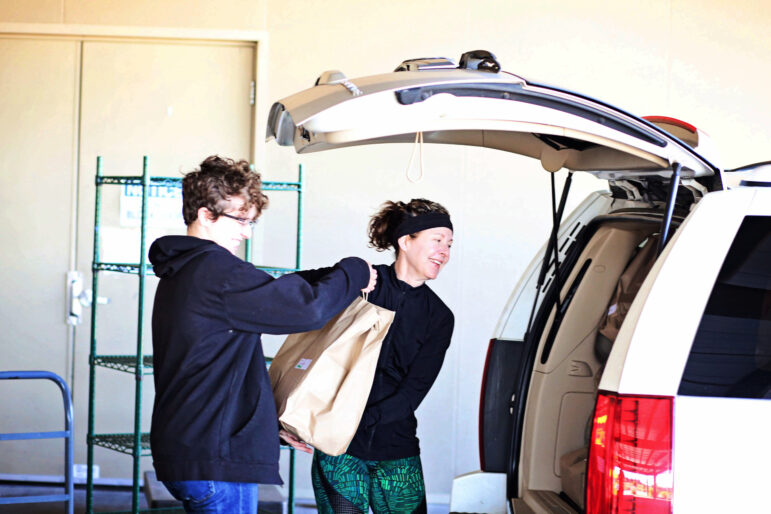 Two volunteers smile as they put a meal bag into the back of their car