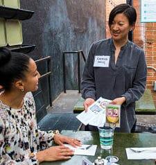Volunteer ambassador talks with a diner
