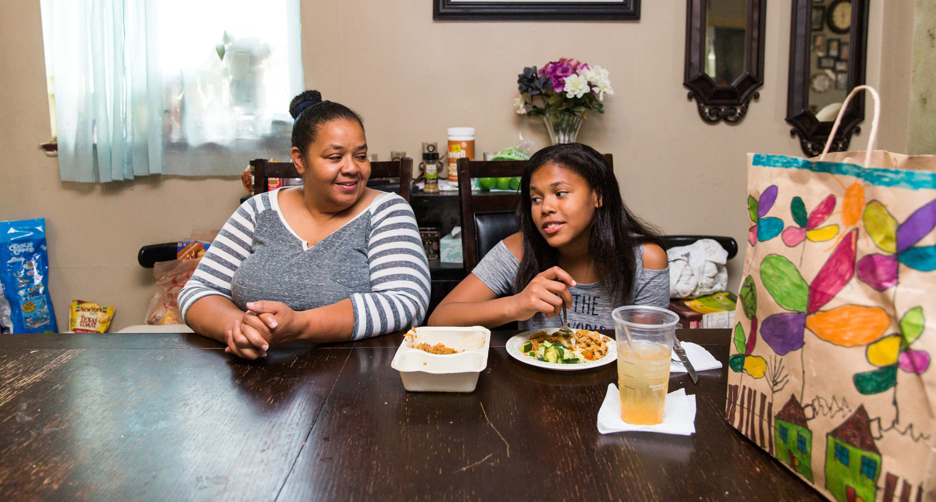 Mom and daughter sitting at the table enjoying a Project Angel Heart meal