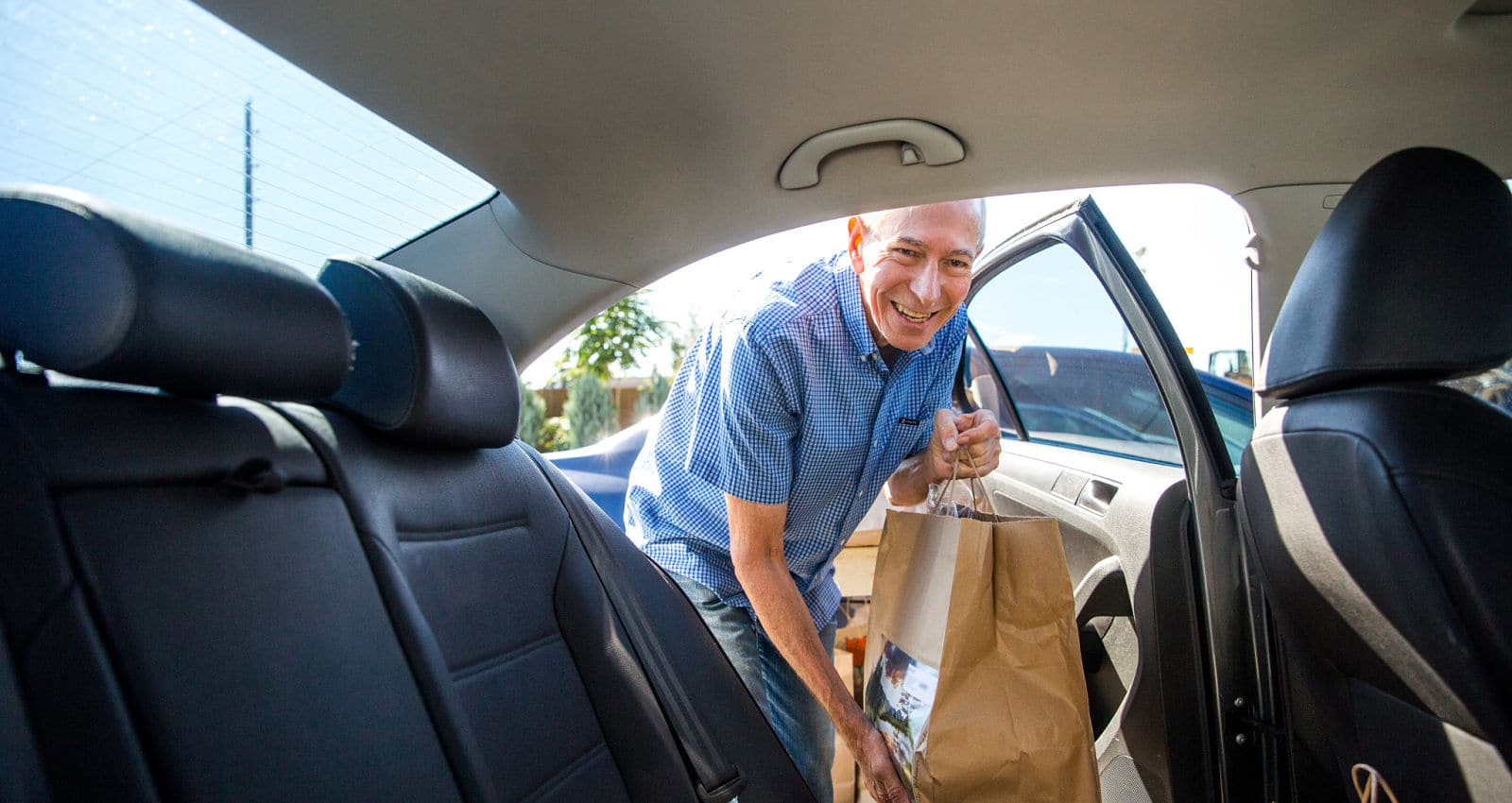 Volunteer loading meal bag into car