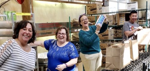 Gina Torres, Project Angel Heart volunteer with friends packing meals for clients