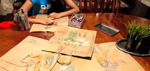 A child drawing on brown paper bags that will accompany medically tailored meals to Project Angel Heart clients.