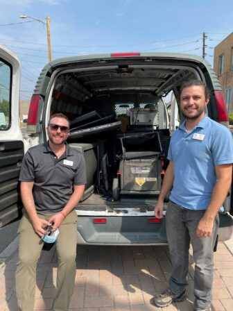 Kyle Copp and Matt Nigro stand in front of a a van that is filled with electronic materials to be recycled.