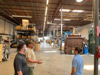 Three men stand in a large recycling warehouse