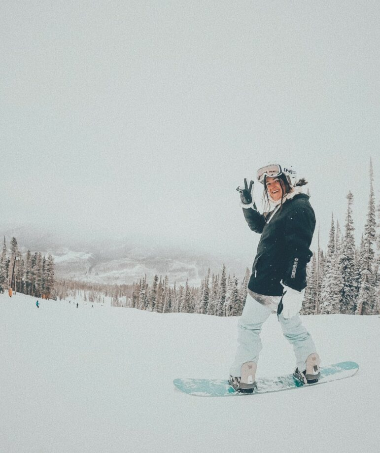 Madison riding a snowboard on a snowy mountain. She is waving at the camera.